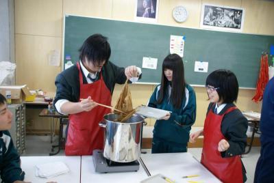 染色鍋から染め物を取り出す