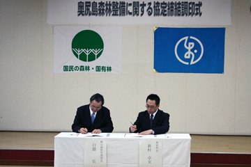 協定書に署名をする新村町長(右)と白淵署長(左)