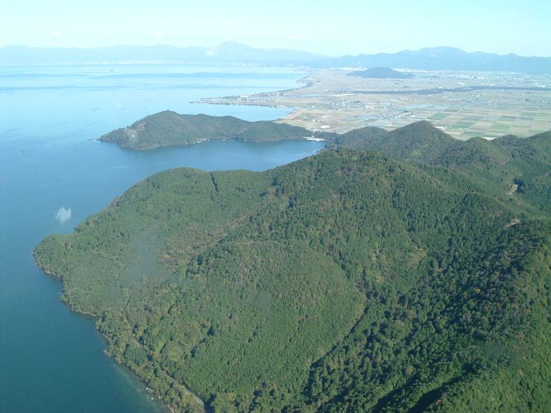 上空から見た奥島山・伊崎国有林、遠くには伊吹山など湖北の山々